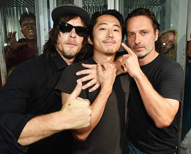 Norman Reedus (Daryl), Steven Yeun (Glenn) and Andrew Lincoln (Rick) stand in front of The Walking Dead display at Comic-Con.